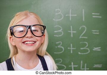 Smart schoolgirl posing in front of a blackboard in a...