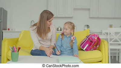 Smart schoolgirl with mum studying at home