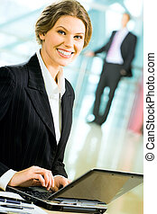 Smart secretary - Portrait of smiling businesswoman sitting ...