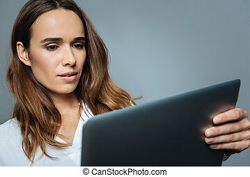 Smart serious businesswoman looking at the laptop screen