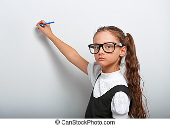 Smart serious pupil kid girl in eyeglasses looking on the wall blue background with drawing pencil