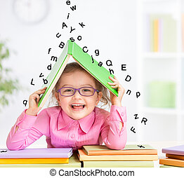 Happy kid in glasses under roof made from book hiding from falling letters