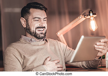 Smart smiling man holding a tablet