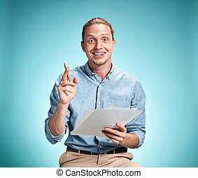 Smart smiling student with great idea holding sheets of...
