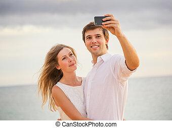 smart, strand, vrouw, liefde, paar, vrolijke , telefoon, man, ondergaande zon , romantische, boeiend, zich, foto