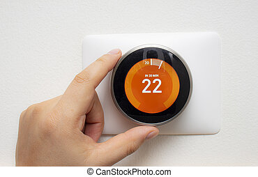 Smart Thermostat with a person warming up the room ...