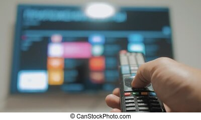 Smart tv with apps and hand. Male hand holding the remote...