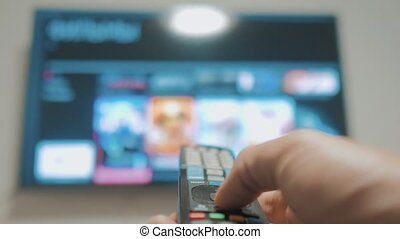 Smart tv with apps and hand. Male hand lifestyle holding the...