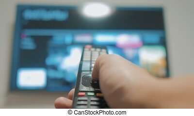 Smart tv with apps and lifestyle hand. Male hand holding the...
