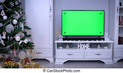 Smart tv with green screen near Christmas tree in living room. Using smart technology on holidays concept. 4k