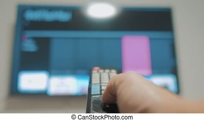 Smart tv with lifestyle apps and hand. Male hand holding the...