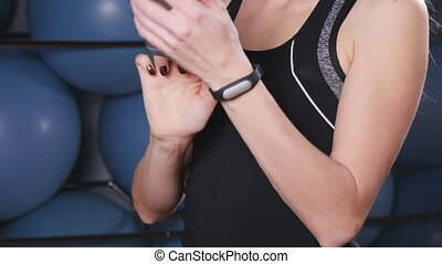 Smart watch showing a heart rate of exercising woman in gym...
