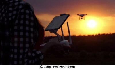 Smart woman keeps a panel to manage her drone at sunset in slo-mo