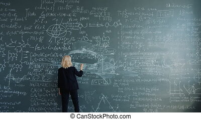 Smart woman researcher is walking to blackboard in classroom writing formulas with chalk focused on science theory. People, education and work concept.
