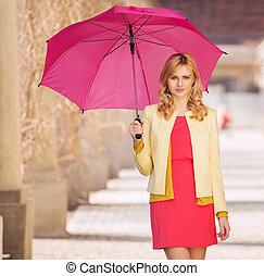 Smart woman waling with umbrella
