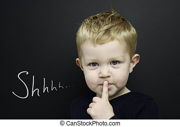 Smart young boy wearing a navy blue jumper stood infront of a blackboard with his finger over his lips being quiet