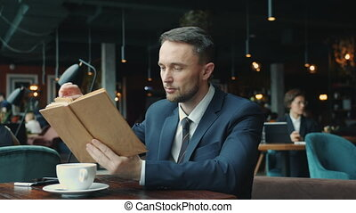 Smart young businessman reading book relaxing at table in ...