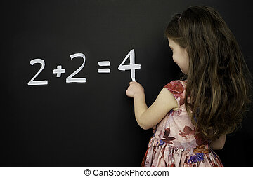 Smart young girl stood writing on a blackboard