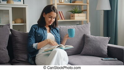Smart young lady reading book holding cup of tea sitting on...