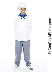 Smart young smiling male chef posing casually