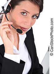 Smart young woman wearing a telephone headset