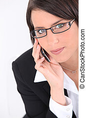 Smart young woman wearing glasses and using a sleek cellphone