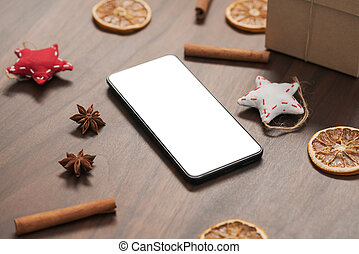 smarthone with white screen and christmas decorations on walnut table, shallow focus