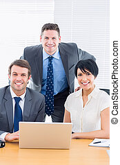 Smartly dressed colleagues with laptop at office desk