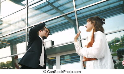 Smartly dressed young man and woman giving high five in a business meeting outdoor