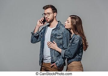 smartphone, óculos, jovem, isolado, cinzento, olhar, falando, tocar, mulher, elegante, homem