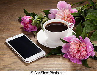 Smartphone, a cup of coffee and flowers on old table