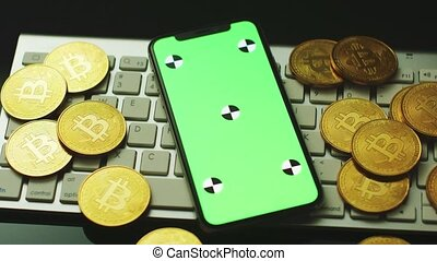 Smartphone and bitcoins on keyboard