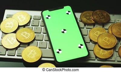 Smartphone and bitcoins on keyboard
