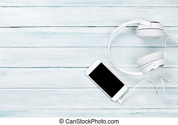Smartphone and headphones on rustic wooden table. Top view with copy space