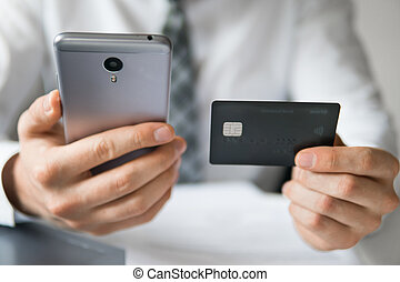 Smartphone and Internet Commerce. Online trading on the currency exchange. Online payments through the phone. Payment of goods online. Young businessman with a bank credit card in his hands.