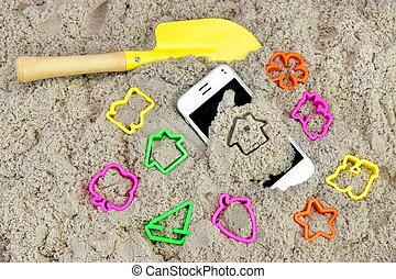 Smartphone And Sand Toys On The Beach Background