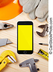Smartphone and set of plumbing and tools on the wooden table