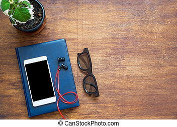 Smartphone, blue notebook, black eyeglasses, red earphones and green flower on wooden table. Top view with copy space