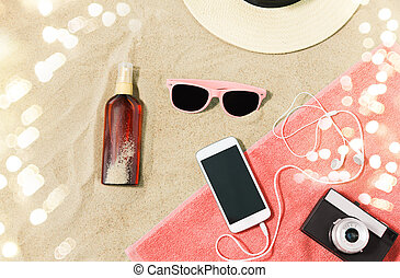 smartphone, camera, towel, hat and shades on beach -...