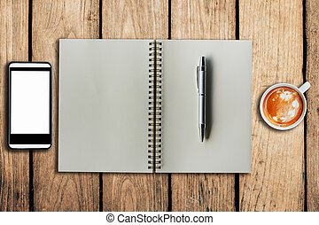 smartphone coffee cup and notebook on wooden background with space.