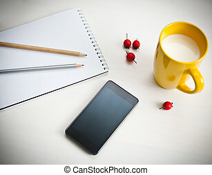 Smartphone, cup of milk and notebook