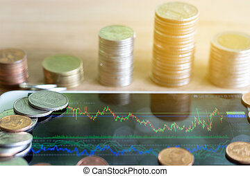 Smartphone display forex chart with coin stack.