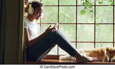 smartphone, elle., séance, américain, écouteurs, écoute, chien, fenêtre, bien élevé, musique, joli, africaine, utilisation, girl, agréable, rebord, mensonge