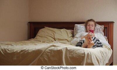 smartphone, femme, mensonge, lit