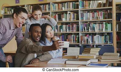 smartphone, groupe, préparer, étudiants, selfie, repos, library., gai, photos, quoique, appareil photo, examen, avoir, confection, amusement, international, sourire, amis, université