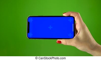 Smartphone in female hand on green screen - Smartphone with...