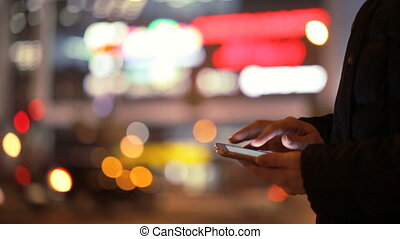 Smartphone in female hands on background of a night city