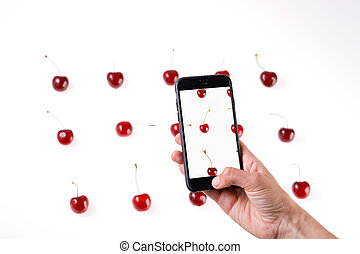 Smartphone in hand. Produces photos of sweet cherry berries on a white background. Juicy summer berries closeup.