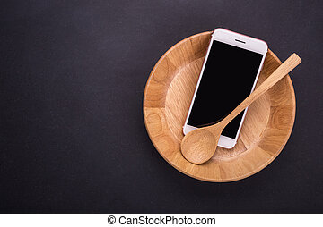 Smartphone in wooden bowl on black stone table background, concept Eating technology