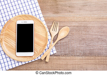 Smartphone in wooden dish, spoon and fork on wooden plank background. Eating technology concept
